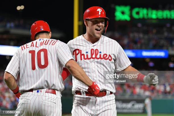 Rhys Hoskins of the Philadelphia Phillies gets congratulated by teammate JT Realmuto after hitting a home run in the eighth inning against the...
