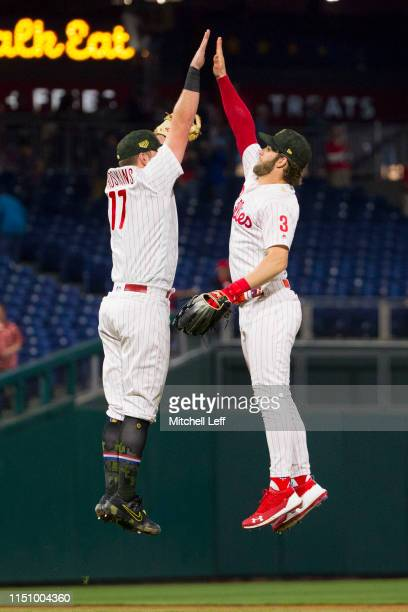 Rhys Hoskins of the Philadelphia Phillies high fives Bryce Harper against the Colorado Rockies at Citizens Bank Park on May 17 2019 in Philadelphia...