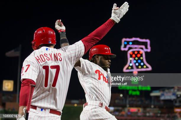 Rhys Hoskins of the Philadelphia Phillies high fives Roman Quinn after Quinn hit a solo homerun in the bottom of the second inning against the Miami...