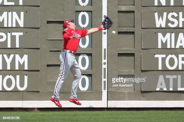 Rhys Hoskins of the Philadelphia Phillies is unable to catch the ball off the bat of Mookie Betts of the Boston Red Sox during a spring training game...