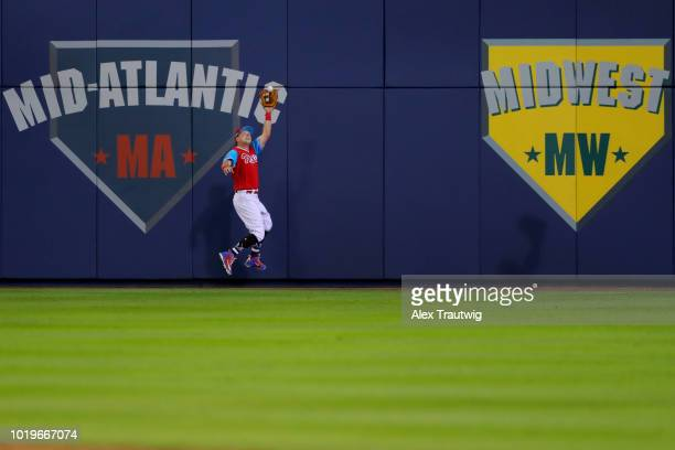 Rhys Hoskins of the Philadelphia Phillies makes a leaping catch against the wall during the 2018 Little League Classic against the New York Mets at...