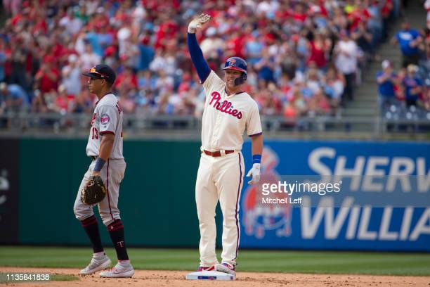 Rhys Hoskins of the Philadelphia Phillies reacts in front of Ehire Adrianza of the Minnesota Twins after hitting a double in the bottom of the eighth...