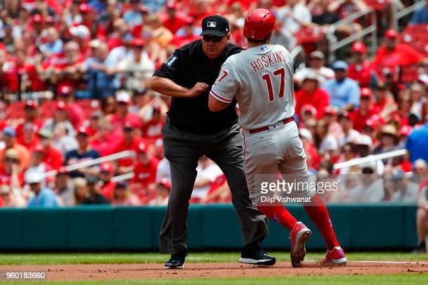 Rhys Hoskins of the Philadelphia Phillies runs into umpire Larry Vanover as he rounds first base against the St. Louis Cardinals in the first inning...