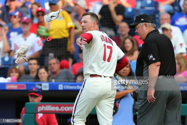 Rhys Hoskins of the Philadelphia Phillies throws his batting gloves as he is being escorted off the field by umpire Joe West after being thrown out...