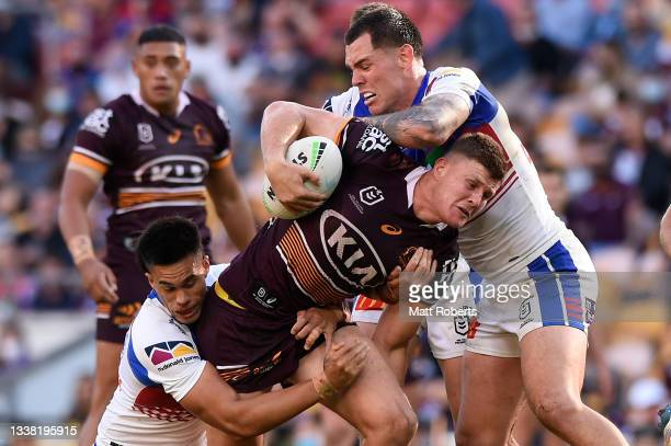 Rhys Kennedy of the Broncos is tackled during the round 25 NRL match between the Brisbane Broncos and the Newcastle Knights at Suncorp Stadium, on...