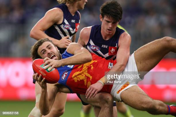 Rhys Mathieson of the Lions gets tackled by Andrew Brayshaw of the Dockers during the round 15 AFL match between the Fremantle Dockers and the...