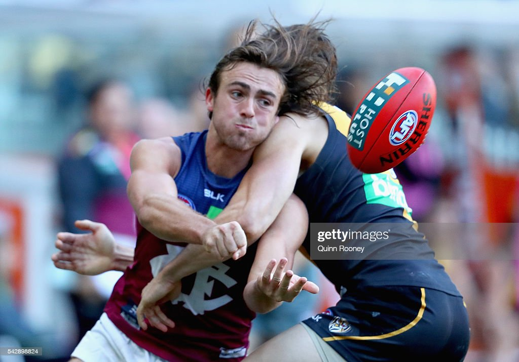 Rhys Mathieson of the Lions handballs whilst being tackled by Brett Deledio of the Tigers during the round 14 AFL match between the Richmond Tigers and the Brisbane Lions at Melbourne Cricket Ground on June 25, 2016 in Melbourne, Australia.