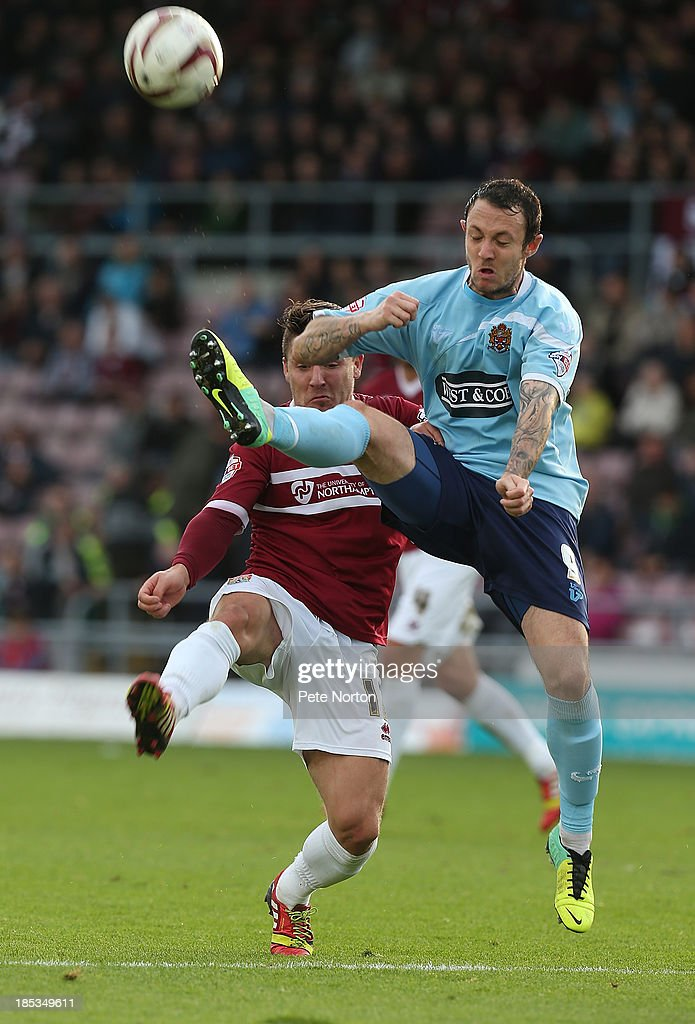 Rhys Murphy of Dagenham & Redbridge clears the ball under pressure from Gary Deegan of Northampton Town during the Sky Bet League Two match between Northampton Town and Dagenham & Redbridge at Sixfields Stadium on October 19, 2013 in Northampton, England.