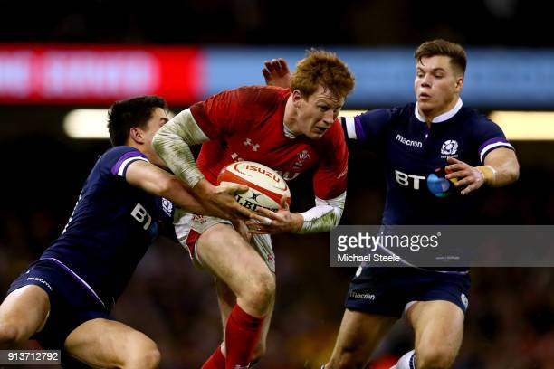 Rhys Patchell of Wales escapes the tackle of Sean Maitland of Scotland and Hue Jones of Scotland during the Natwest Six Nations round One match...