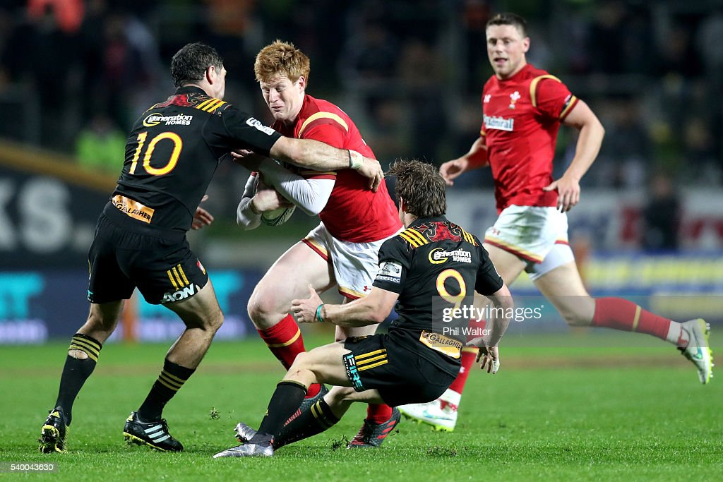 Rhys Patchell of Wales is tackled by Stephen Donald (L) and Brad Weber (R) of the Chiefs during the International Test match between the Chiefs and Wales at Waikato Stadium on June 14, 2016 in Hamilton, New Zealand.