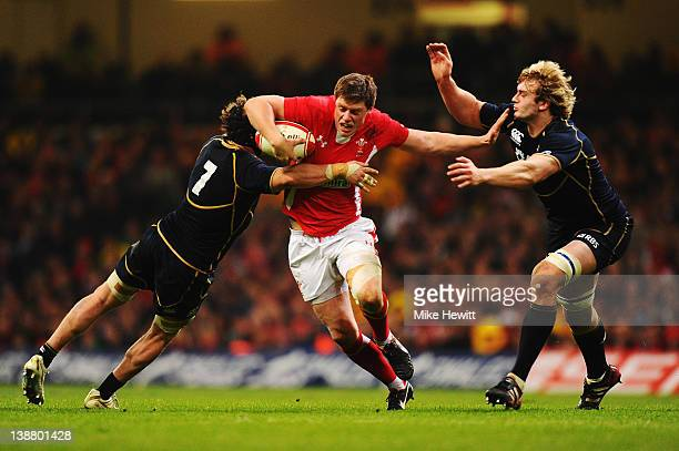 Rhys Priestland of Wales holds off the challenge of Ross Rennie and Richie Gray of Scotland during the RBS Six Nations match between Wales and...