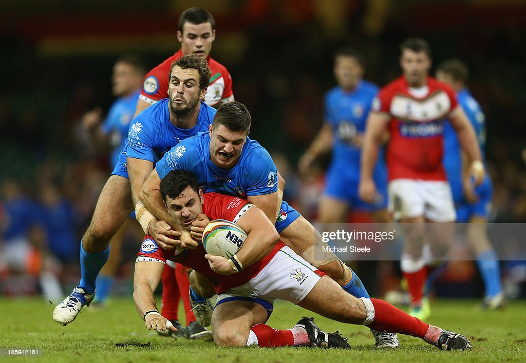Rhys Williams of Wales is tackled by James Tedesco and Joshua Mantellato of Italy during the Rugby League World Cup Inter group match between Wales and Italy at the Millennium Stadium on October 26, 2013 in Cardiff, Wales.