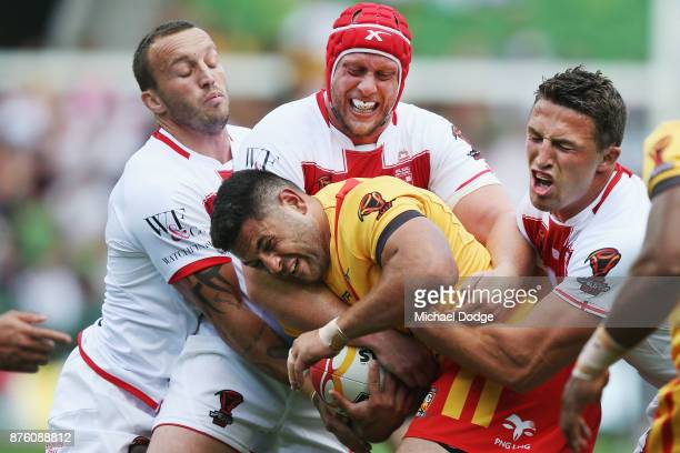 Rhyse Martin of Papua New Guinea is tackled by Luke Gale Chris Hill and Sam Burgess of England during the 2017 Rugby League World Cup Quarter Final...