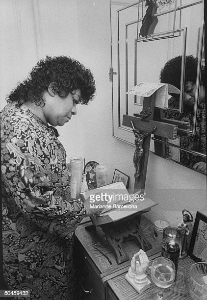 Rhythm blues singer Ruth Brown popular in '50's enjoying comeback seen at home reading Bible in religious corner of home and paying respects to late...