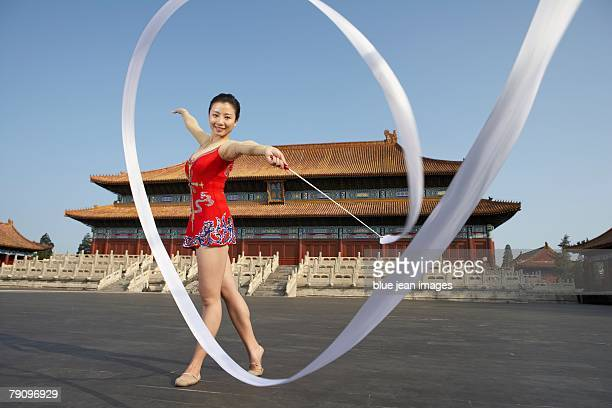 a rhythmic gymnastics athlete practices in front of an ancient, ming dynasty-style chinese temple square, early morning. - gymnastique au sol photos et images de collection