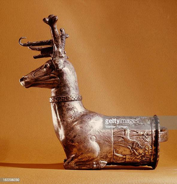 A rhyton in the form of a stag The relief is decorated with three figures making offerings to the king or the queen who stands on the back of deer...