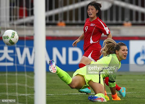 Ri Hyang Sim of Korea DPR beats Casey Murphy of the United States to score her teams second goal during the FIFA U20 Women's World Cup Papua New...
