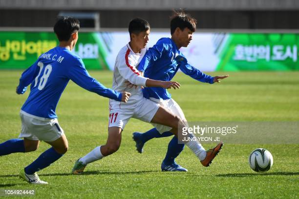Ri Il Song of the April 25 Sports Club of North Korea fights for the ball against players from the Gangwondo team of South Korea during their match...