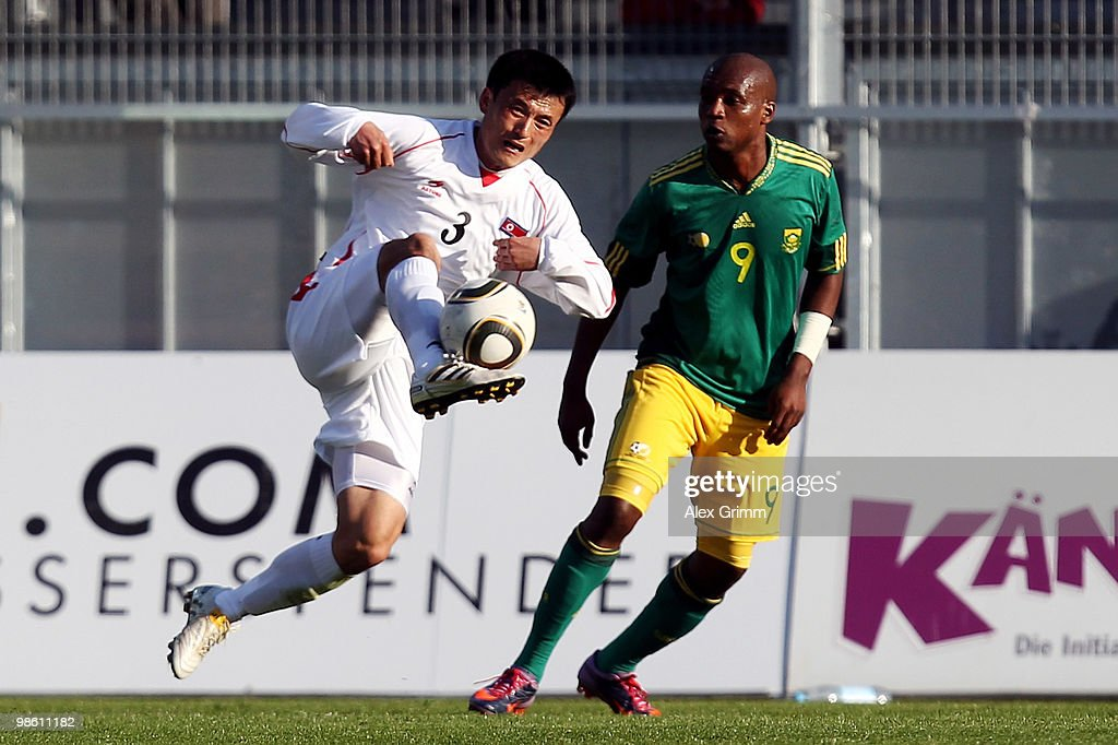 Ri Jun Il (L) of North Korea is challenged by Katlego Mphela of South Africa during the international friendly match between South Africa and North Korea at the Brita arena on April 22, 2010 in Wiesbaden, Germany.
