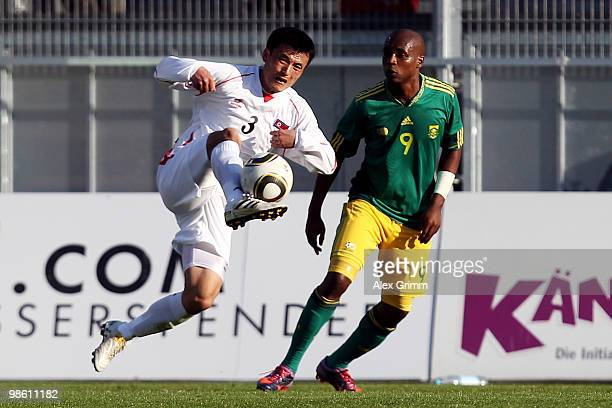 Ri Jun Il of North Korea is challenged by Katlego Mphela of South Africa during the international friendly match between South Africa and North Korea...