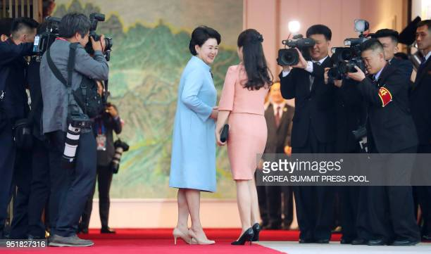 Ri Sol Ju wife of North Korea's leader Kim Jong Un is greeted by Kim Jungsook wife of South Korea's President Moon Jaein before the official dinner...