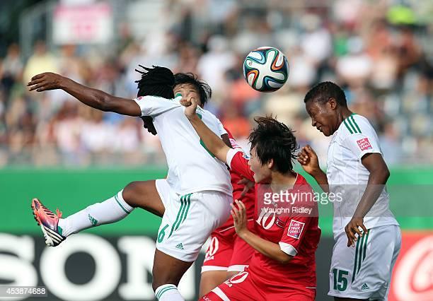 Ri Un Sim of Korea DPR battles for a high ball with Sarah Nnodim and Ugo Njoku of Nigeria during the FIFA U20 Women's World Cup Canada 2014 Semi...