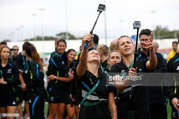 Ria Percival and Meikayla Moore take photos during their official welcome and flag raising ceremony in the Athletes Village to the Rio Olympics on...