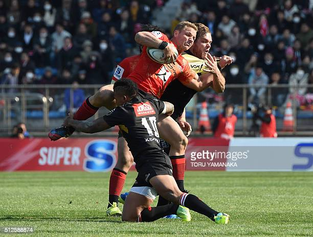 Riaan Viljoen of the Sunwolves is tackled by Elton Jantjies and Andries Ferreira of the Lions during the round one Super Rugby match between the...