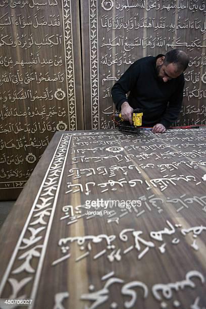 Riad Nawaf Al Radi a Syrian refugee from Daraa works to make the largest edition of the holy Muslim text the Quran on wood panels on March 26 2014 in...