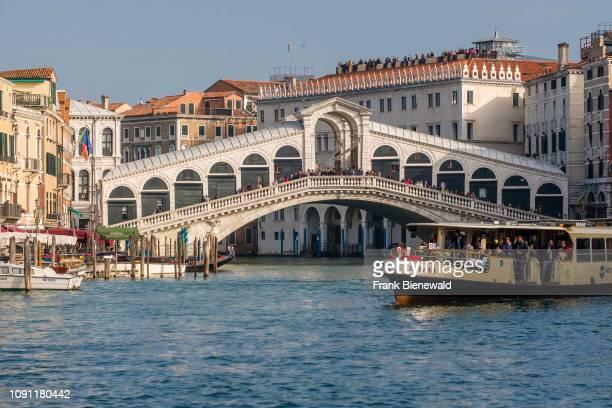 Rialto Bridge, Ponte di Rialto, a stone arch bridge, spanning the Grand Canal, Canal Grande, a local ferryboat crossing.