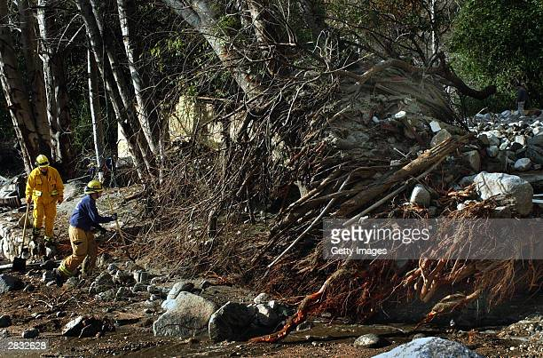Rialto firefighters Waylan Kruse and Dave Denman search among a pile of debris and tree trunks at the Saint Sophia Camp after a mudslide December 26,...
