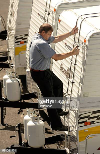 Rialto, Sept. 21, 2005 – – Ron Richardson, general manager, Fleetwood Enterprises Inc., climbs up a finished travel trailer at the in Rialto. Work is...