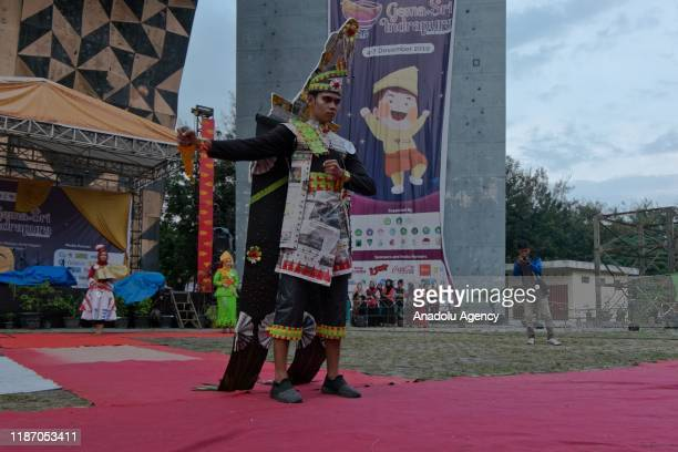 Riau University student showcases clothing made of recycled waste such as plastics and papers as a part of environmental campaign in Pekanbaru Riau...