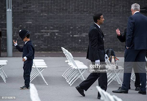 Riaz Hoque tries on his dad's police hat as his father Anowarul Hoque walks past empty chairs before the start of the Metropolitan Police 'Passing...
