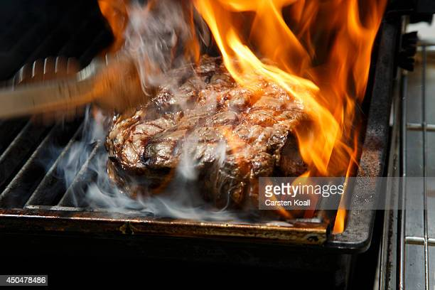 A rib eye steak is cooked in a short fire on the grill during a cooking demonstration at a barbecue in the courtyard of the US Embassy on Pariser...