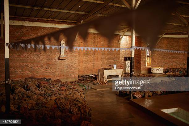 Ribbon and pennant banners are hung above piles of genocide victims' clothing inside the Nyamata Catholic Church memorial ahead of the 20th...