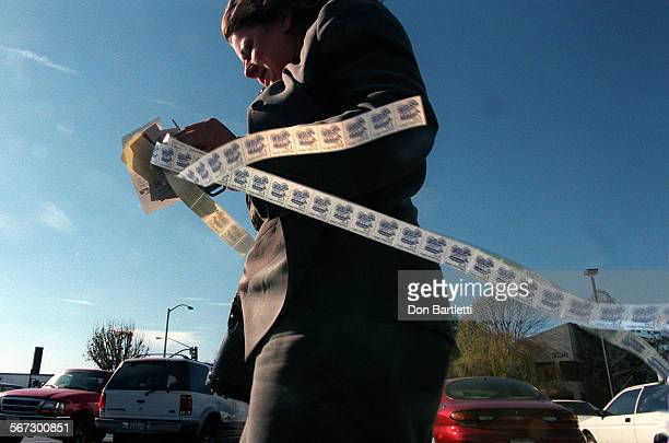 A ribbon of eighty 1–cent stamps flutters in the wind as Kristan Willis hussles through the parking lot of the Santa Ana California branch of the...