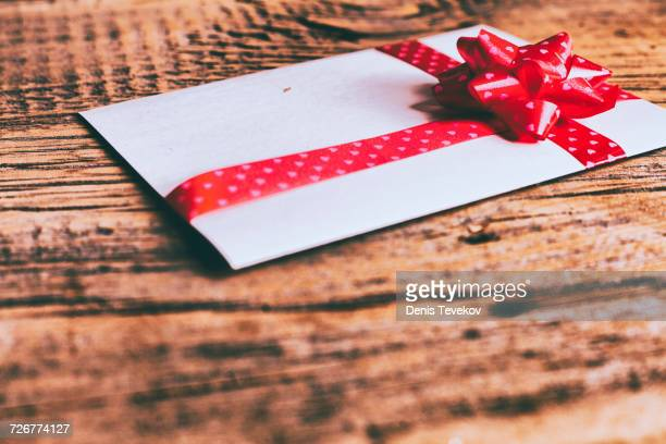 Ribbon on valentine card on wooden table