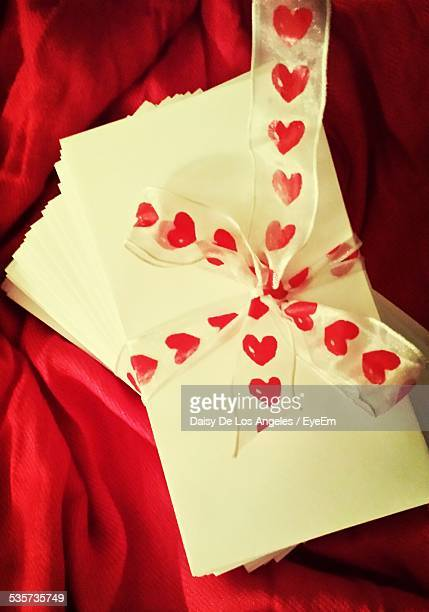 ribbon tied to paper on red cloth - love letter stock photos and pictures