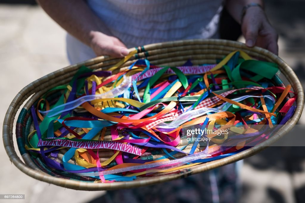 Ribbons are offered to members of the public to symbolically tie onto a piece of netting during a 'Great Get Together' community service and picnic in memory of murdered Member of Parliament Jo Cox, marking the first anniversary since her killing, in the grounds of All Saints Church in Batley, northern England on June 18, 2017. The Great Get Together weekend is Inspired by murdered Labour MP Jo Cox's belief that we have more in common than which divides us, a line from her first speech to Parliament, and is a community initiative designed to unite people and communities on the streets and parks of their neighbourhoods. The 41 year-old Labour Party MP, Jo Cox, was assassinated by a pro-Nazi sympathiser in a terror attack in her constituency in northern England on June 16, 2016. /