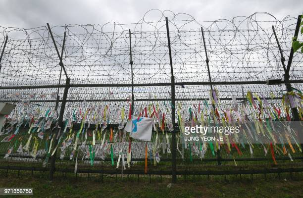 Ribbons with inscriptions calling for peace and reunification are displayed on a military fence at Imjingak peace park near the Demilitarised Zone...