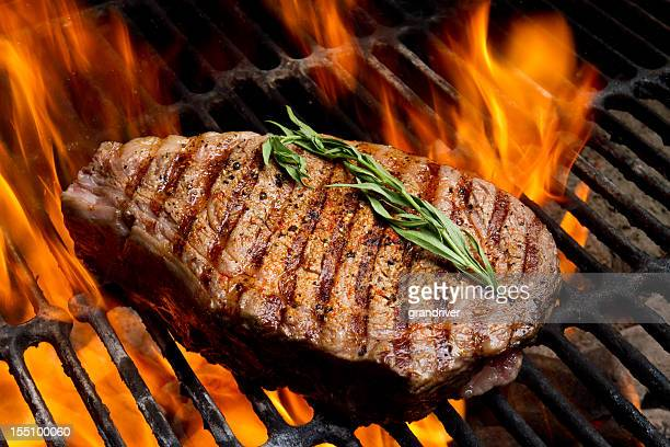 ribeye steak on grill with fire - meat stock pictures, royalty-free photos & images