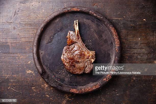 Ribeye Steak with salt and pepper on dark wooden background