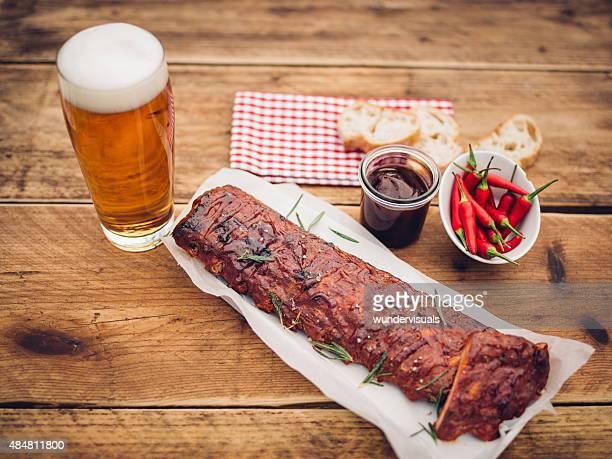 costillas con salsa chillies y una altura de vidrio de cerveza - barbeque sauce fotografías e imágenes de stock