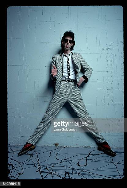 Ric Ocasek, lead singer/songwriter with the rock and roll group The Cars, is shown standing against a wall, wearing a checkered or houndstooth suit...