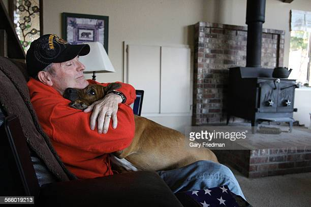 Ric Ryan hugs his dog 'Hanes' in his home in Murphys California in Calaveras County on February 23 2013 Known as the 'The Walking Man of Muphys' Ryan...