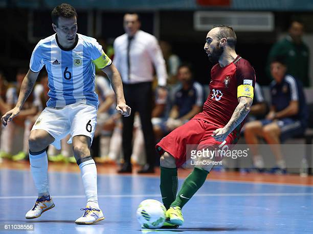 Ricardinho of Portugal plays the ball as Fernando Wilhelm of Argentina defends during a semi final match between Argentina and Portugal as part of...