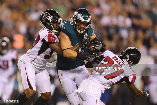 Ricardo Allen and Damontae Kazee of the Atlanta Falcons attempt to tackle Zach Ertz of the Philadelphia Eagles during the second half at Lincoln...