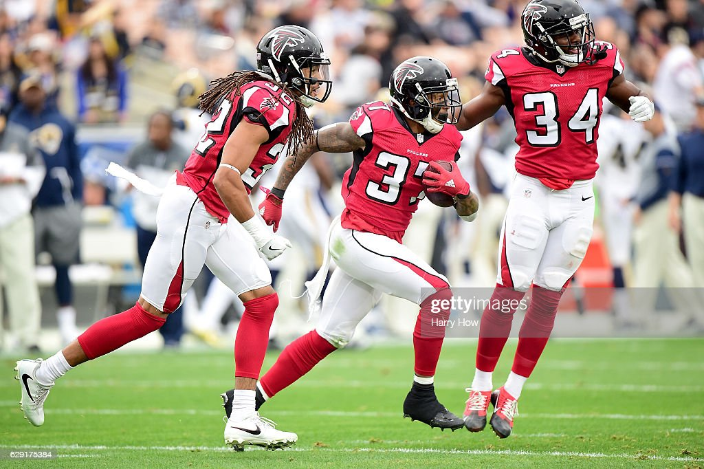 Ricardo Allen #37 of the Atlanta Falcons celebrates his interception with Brian Poole #34 and Jalen Collins #32 during the first quater against the Los Angeles Rams at Los Angeles Memorial Coliseum on December 11, 2016 in Los Angeles, California.
