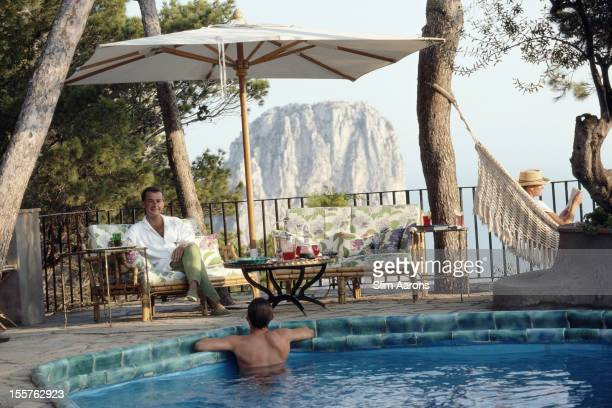 Ricardo Bolliger sitting beside a swimming pool on the island of Capri Italy in September 1989 A man leans against the side of the pool and a woman...